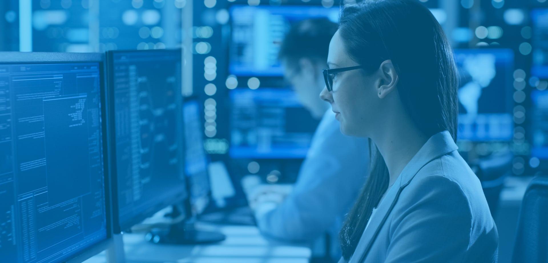 Une femme est assise à un poste informatique.
