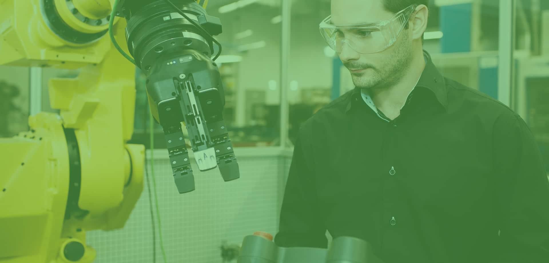 Un technicien opère une cellule robotisée.
